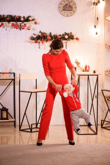 Madre alla moda che gioca con il bambino in cappello della santa che si siede sul pavimento vicino alle decorazioni di natale Foto Premium