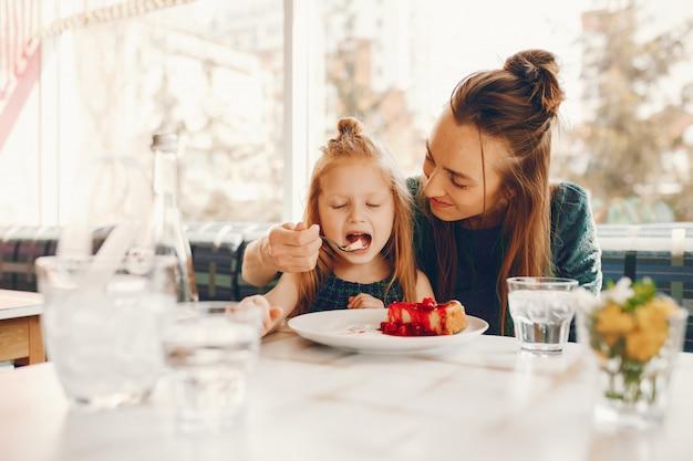 Madre alla moda con i capelli lunghi e un vestito verde seduto con la sua piccola figlia carina Foto Gratuite