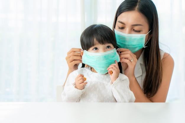 Madre asiatica che indossa indossando a sua figlia una maschera per il viso sana seduta nel salotto di casa per prevenire polvere pm2.5, smog, inquinamento dell'aria e covid-19. Foto Premium
