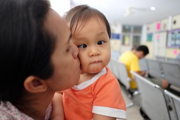Madre asiatica che trasporta un bambino. Foto Premium