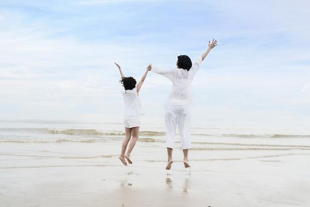 Madre asiatica con la figlia che si tiene per mano, divertendosi e saltando sulla spiaggia. Foto Premium