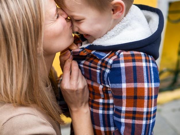 Madre bionda del primo piano che bacia il suo giovane ragazzo Foto Gratuite