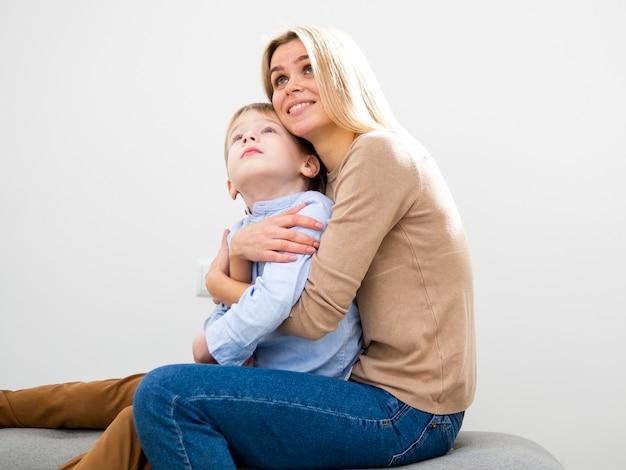 Madre bionda di vista frontale che abbraccia suo figlio Foto Gratuite