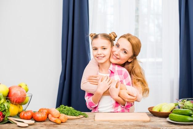 Madre che abbraccia sua figlia in piedi dietro il tavolo di legno con verdure fresche Foto Gratuite