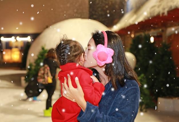 Madre che bacia sua figlia nella neve, orario invernale. Foto Premium