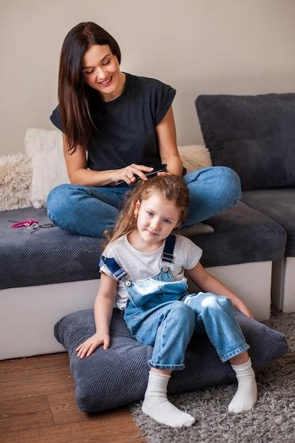 Madre che disegna i suoi capelli carini figlie Foto Gratuite
