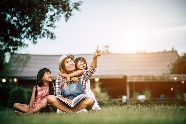Madre che racconta una storia a due figliolette nel giardino di casa Foto Gratuite