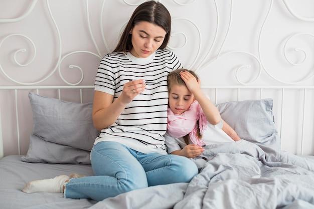 Madre che si prende cura di sua figlia malata Foto Gratuite