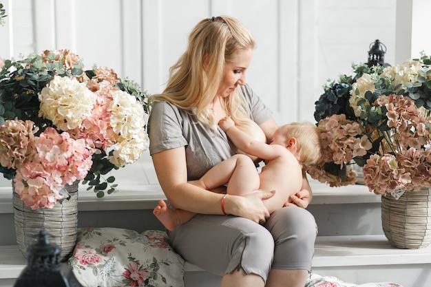 Madre che tiene in braccio un bambino prima di allattare. studio sparato nell'arredamento dei fiori Foto Gratuite