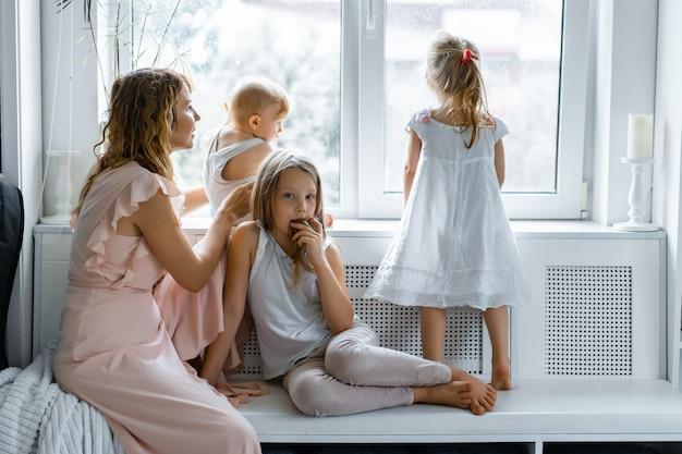 Madre con bambini in un'atmosfera familiare. bambini vicino alla finestra Foto Gratuite