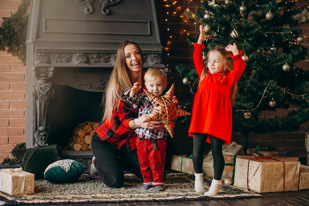 Madre con bambini per albero di natale Foto Gratuite