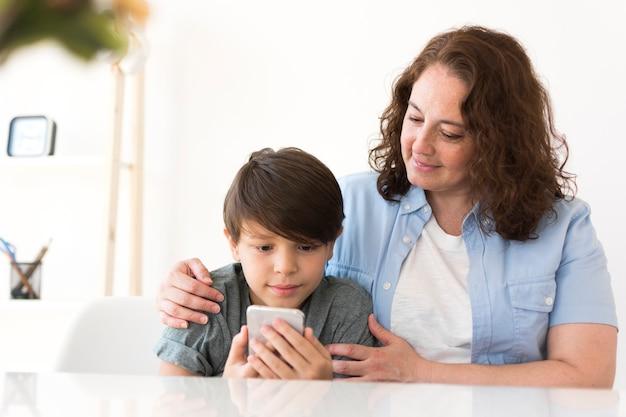 Madre con bambino alla ricerca di smartphone Foto Gratuite
