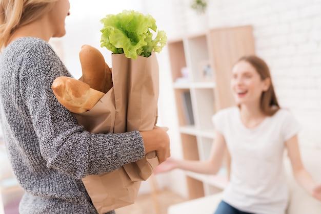 Madre con confezioni di cibo dal negozio a casa. Foto Premium