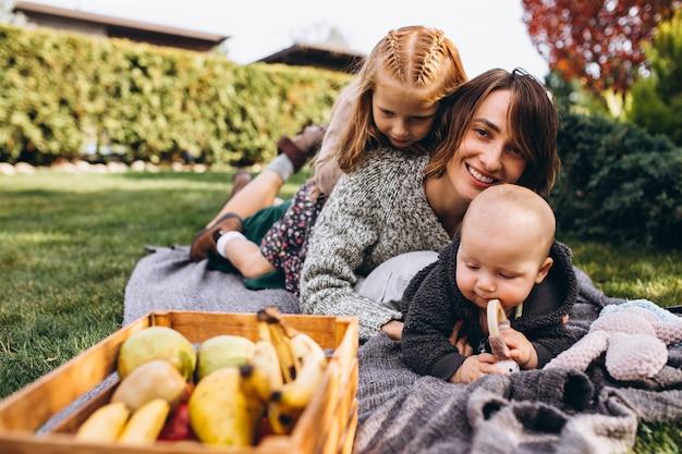 Madre con due bambini che hanno picnic su un cortile Foto Gratuite