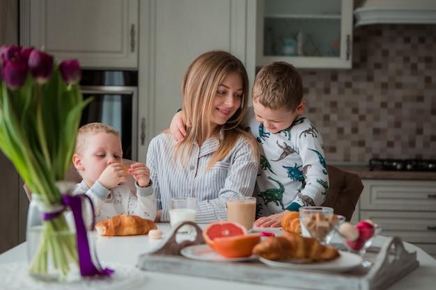 Madre con figli facendo colazione in cucina Foto Premium
