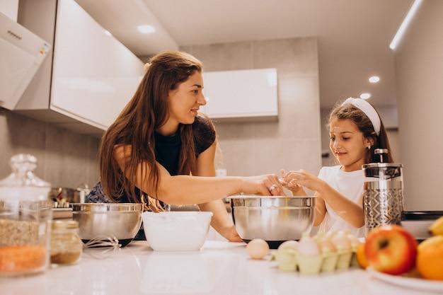 Madre con figlia cottura in cucina insieme Foto Gratuite
