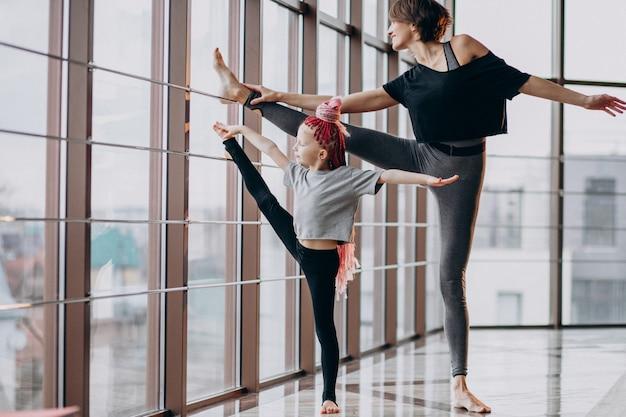 Madre con figlia piccola a praticare yoga vicino alla finestra Foto Gratuite