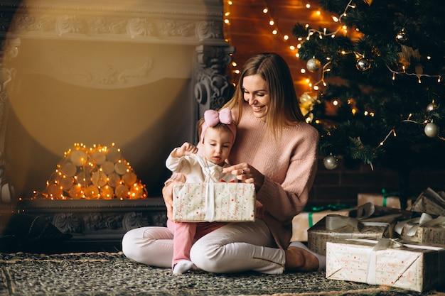 Madre con la figlia che disimballa i regali di natale dall'albero di natale Foto Gratuite