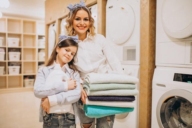 Madre con la figlia che fa lavanderia alla lavanderia automatica del self service Foto Gratuite
