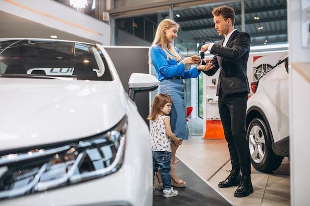 Madre con la figlia che parla con addetto alle vendite in una sala d'esposizione dell'automobile Foto Gratuite