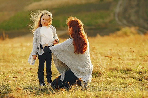 Madre con la piccola figlia che gioca in un campo di autunno Foto Gratuite