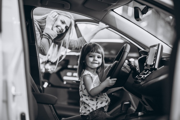 Madre con la piccola figlia che si siede in un'automobile in una sala d'esposizione dell'automobile Foto Gratuite