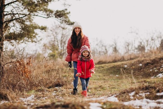 Madre con la piccola figlia in una foresta di inverno Foto Gratuite