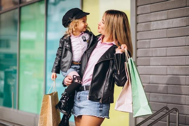 Madre con la sua piccola figlia carina con borse della spesa Foto Gratuite