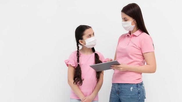 Madre con maschera tenendo la tavoletta Foto Gratuite