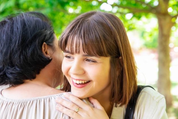 Madre d'abbraccio sorridente della giovane donna in parco Foto Gratuite