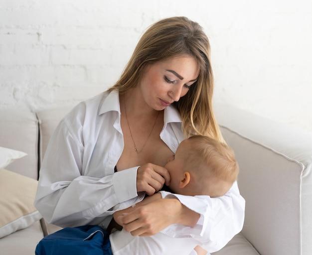 Madre del colpo medio che allatta al seno il suo bambino Foto Gratuite