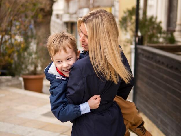 Madre di vista frontale che tiene giovane ragazzo all'aperto Foto Gratuite