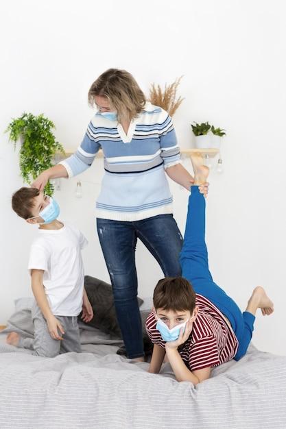 Madre e bambini che giocano insieme indossando maschere mediche Foto Gratuite