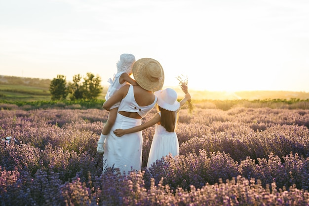 Madre e due ragazze guardano verso il tramonto nel campo di lavanda Foto Premium