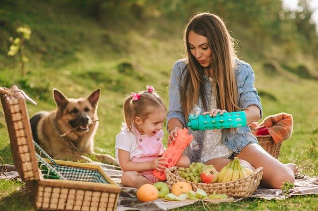 Madre e figlia a un picnic con un cane Foto Premium
