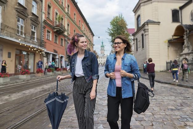 Madre e figlia adolescente che camminano sulla strada della città Foto Premium