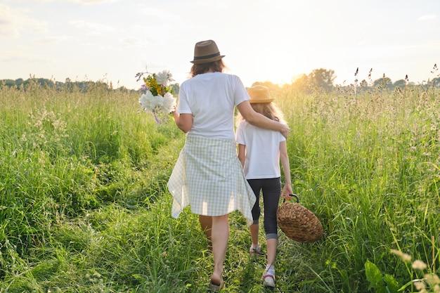 Madre e figlia bambino che cammina lungo il prato, vista dal retro Foto Premium