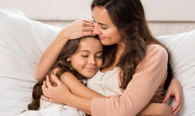 Madre e figlia che abbracciano nel letto Foto Gratuite