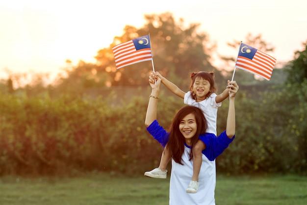 Madre e figlia che alzano bandiera della malesia Foto Premium
