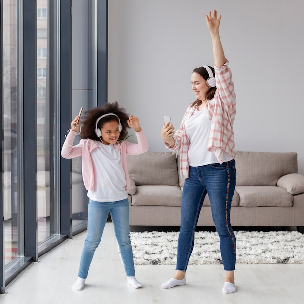Madre e figlia che ballano alla musica a casa Foto Gratuite