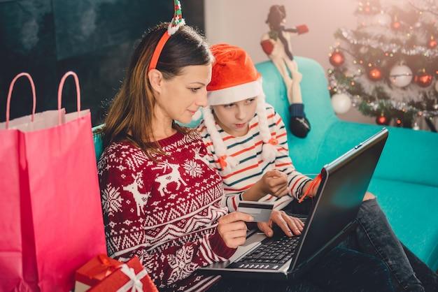 Madre e figlia che comperano online a casa durante il natale Foto Premium