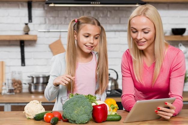 Madre e figlia che esaminano una compressa digitale Foto Gratuite