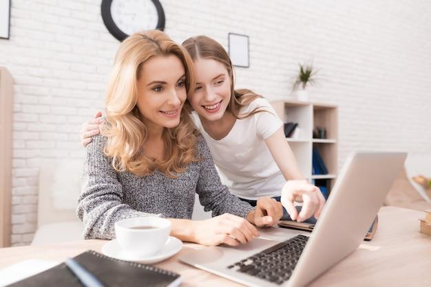 Madre e figlia che guardano nel computer portatile a casa. Foto Premium