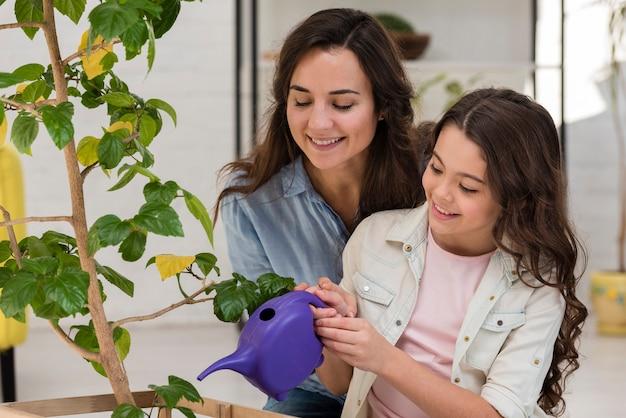 Madre e figlia che innaffiano la pianta insieme Foto Gratuite