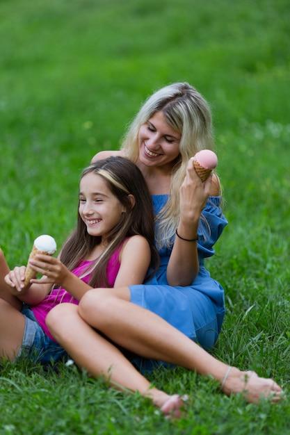 Madre e figlia che mangiano il gelato in parco Foto Gratuite