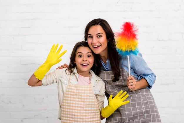 Madre e figlia che posano con gli oggetti di pulizia Foto Gratuite