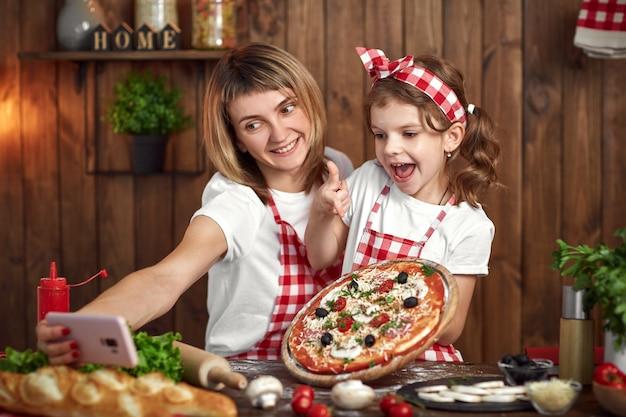 Madre e figlia che prendono selfie con pizza sullo smartphone Foto Premium