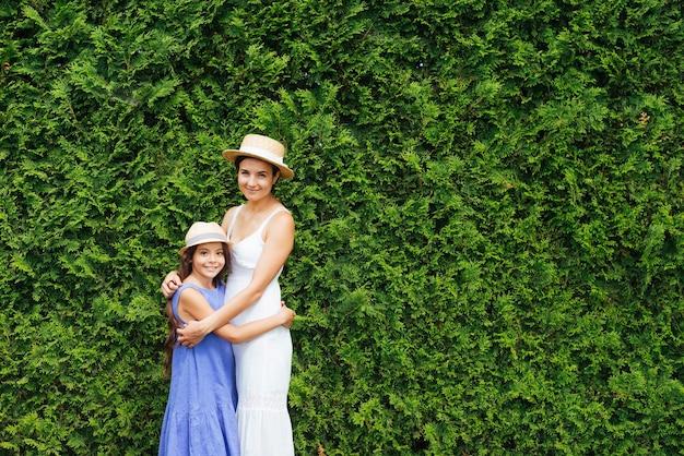 Madre e figlia che si abbracciano davanti ai cespugli Foto Gratuite