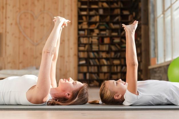 Madre e figlia che si estendono sulla stuoia di yoga Foto Gratuite