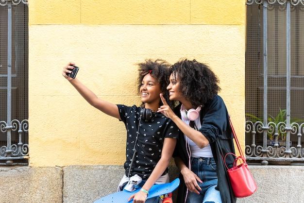 Madre e figlia che si prendono un selfie insieme. Foto Premium